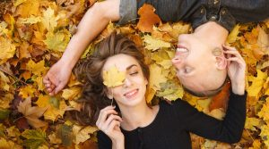 A man and a woman laying in a pile of leaves
